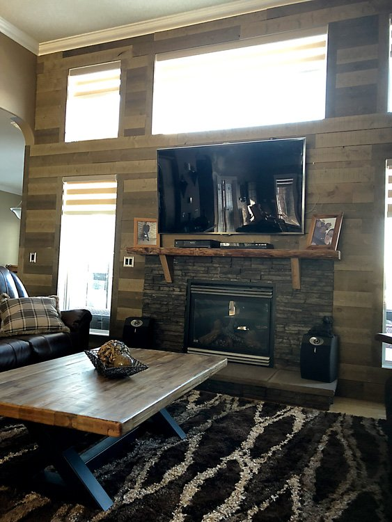 Renovated Living room with feature barn board wall and renovated fireplace with stone surround by Ingram Renovations