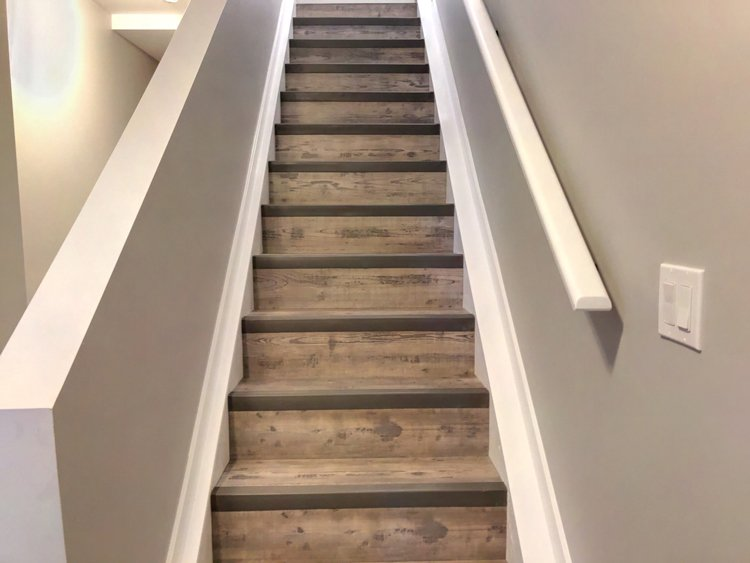 Stairway in Basement Development by Ingram Renovations with light grey flooring wide white baseboards