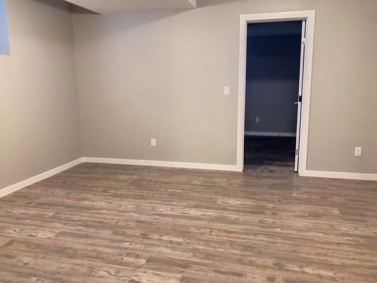 Basement Development by Ingram Renovations with light grey flooring wide white baseboards and contemporary doors & hardware
